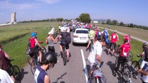 Zmätok na ceste, medzi cyklistami uviazlo auto, ktoré nik nevaroval, že sa koná mega cykloakcia.
